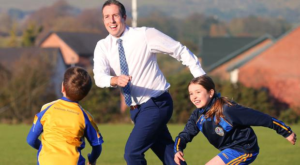 Communities Minister Paul Givan has a go at Gaelic football during a visit to St Patrick's GAC in Lisburn yesterday