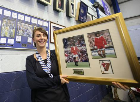 Amber McCullough from Wilsons Auctions with signed photos of George Best