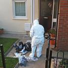 Forensic officers attend the scene of the arson attack on a pensioner's house in Newtownards