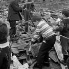 Children remove a baby's cot from the debris of McGurk's bar in North Queen Street, Belfast, where 15 people died in 1971