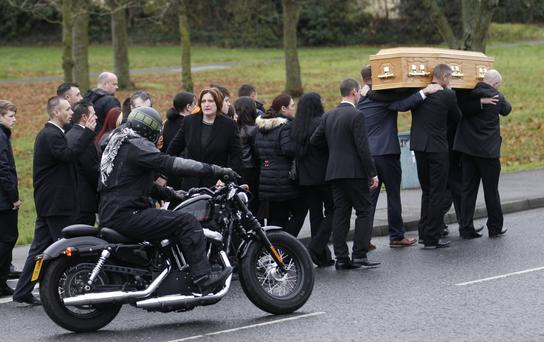 Motorbike riders escort the cortege of Barry Bell-Nevin as family and friends carry his coffin from his mother's home in Ballynahinch