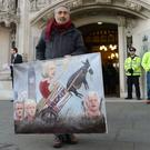 Satirical artist Kaya Mar with one of his political paintings outside the Supreme Court in London