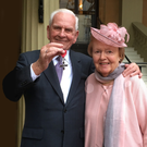 Stanley McIlroy and wife Noreen at Buckingham Palace to accept his MBE for dedication to fundraising for Cancer Research UK and other charities.