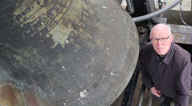 Father Delargy with the bell, which is now working after restoration
