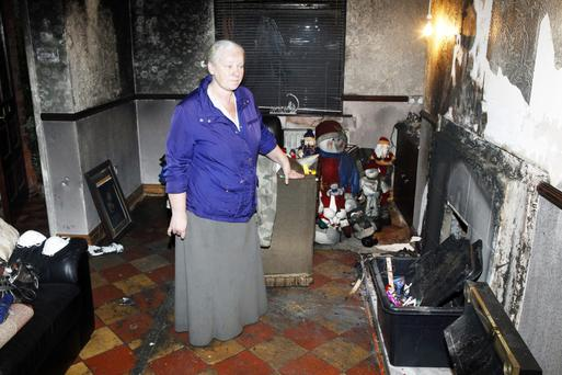 Anne-Marie McCann in her badly damaged living room. Photo: Peter Morrison