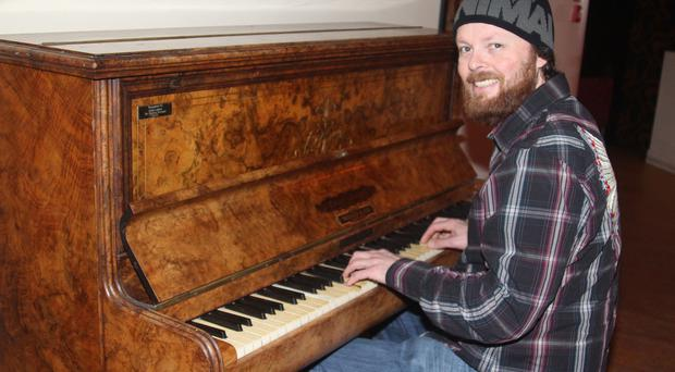 Kris Charteris playing The John Lennon piano in his Kiwi's Bar in Portrush