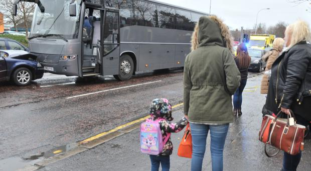 Parents and children look on after a bus and a car were caught in the head-on crash
