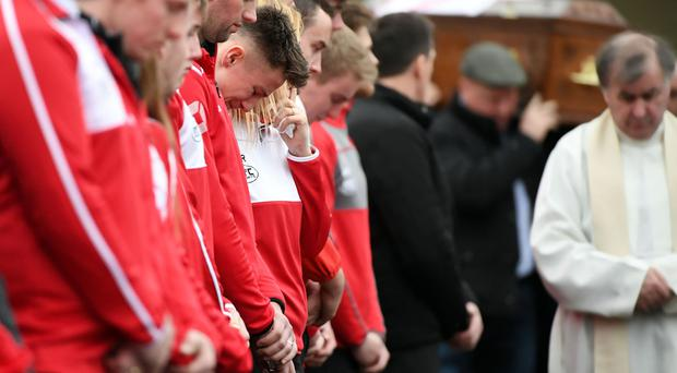 Killian's friends from his GAA club weep as his coffin is carried from church