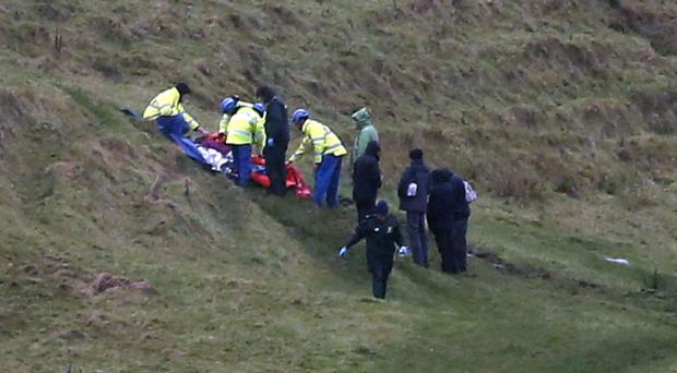 Rescuers and paramedics aid the woman who sustained leg injuries at Ballintoy Harbour