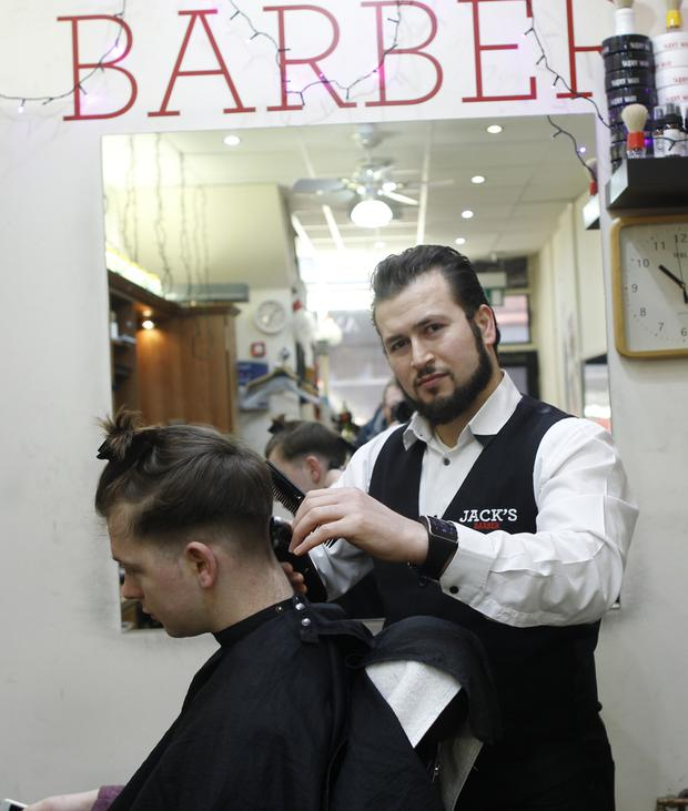 Barber Jack Shewihi in his shop on Church Lane, Belfast