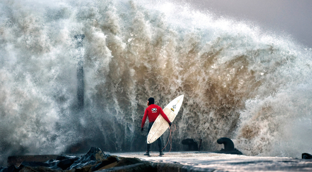 A huge wave crashes against Castlerock pier yesterday as professional surfer Al Mennie waits for a break in the swell (Picture Charles McQuillan/Getty)