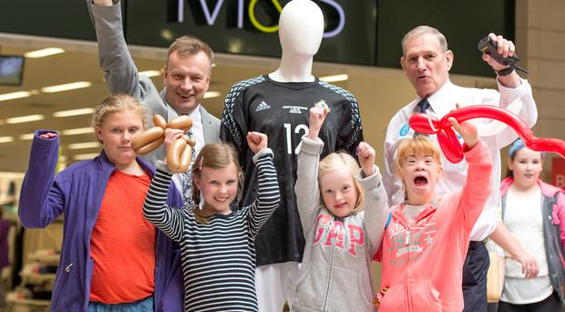 Tiffany Downey, Ami Gilliland, Grainne Haughey and Rachel McGuinness give a big cheer as Erneside Shopping Centre manager Jim Masterson (left) and Erneside security officer Bob Carroll, father of NI player Roy, display the substitute goalie's jersey from the Euro 2016 game against Ukraine, which is going under the hammer for charity