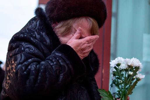 A woman weeps as she holds flowers at the home stage building of the Alexandrov Ensemble in Moscow