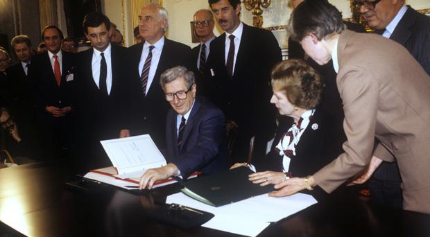 Taoiseach Garret FitzGerald, left, and Prime Minister Margaret Thatcher prepare to sign the Anglo-Irish Agreement