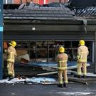 Firefighters examine the damage caused to the petrol station on the Stewartstown Road