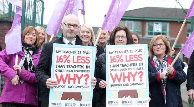 Teachers outside St Therese of Lisieux Primary School in north Belfast during the half-day strike yesterday