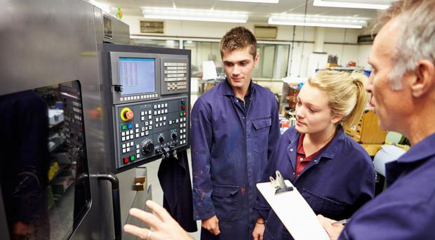 Engineering apprentices learn to use a computerised lathe
