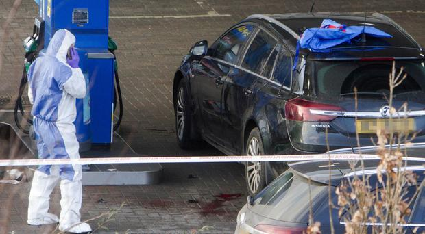 A PSNI forensics team at the petrol station on the Crumlin Road yesterday where a police officer was shot on Sunday evening