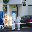 Forensic officers attend the scene on the Crumlin Road Belfast where a PSNI officer was shot