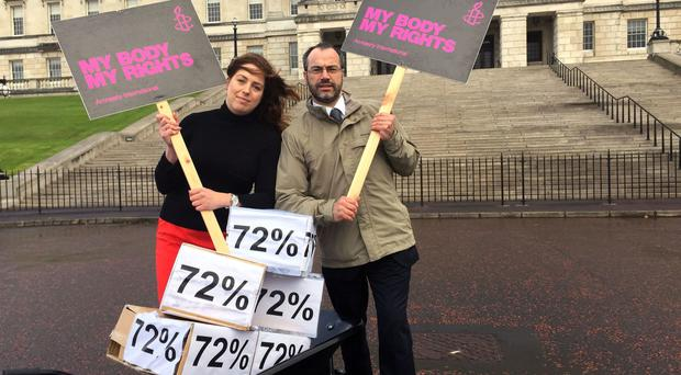 Adrianne Peltz and Patrick Corrigan from Amnesty International deliver a petition of 45,000 signatures calling for a change on Northern Ireland's abortion laws to Parliament Buildings in Belfast