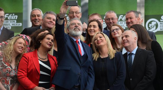 Sinn Fein president Gerry Adams taking a selfie alongside Michelle O'Neill and election candidates at the party's Waterfront Hall Press conference