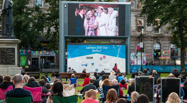 People gather to watch a film on the Big Screen at Belfast City Hall