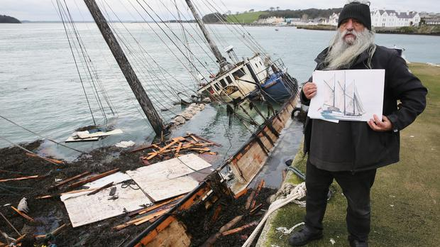 William Mulhall, owner of the historic Tall Ship Regina Caelis, holds a photograph of the ship at Strangford Lough (Brian Lawless/PA Wire)