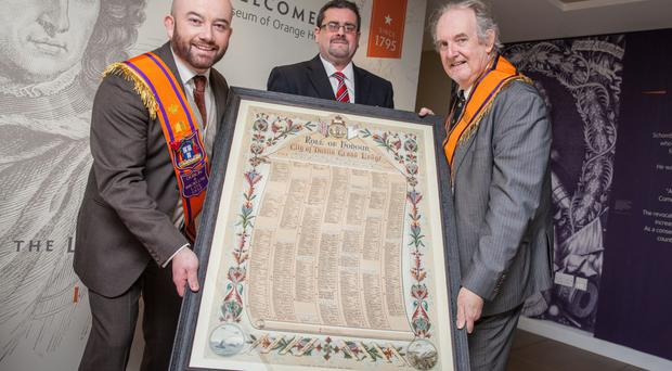 Dr Chris McGimpsey (right) and Chris Thackaberry from Dublin and Wicklow LOL 1313 present the roll of honour to Museum of Orange Heritage curator Dr Jonathan Mattison (centre)