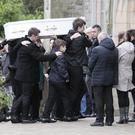 The white coffin of Bronagh Kinney is carried into St Mary's Church in Cushendall