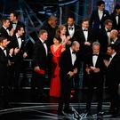 Puzzled La La Land producers look at the card for Best Film held by Warren Beatty