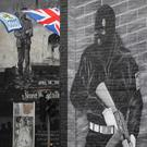 A mother and young boy walk past a loyalist terrorist mural