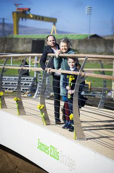 James Ellis' wife Robina, son Toto and Victoria McCullough from Victoria Primary School at the opening of the new James Ellis bridge in east Belfast. Inset, an emotional Robina is comforted by son Toto