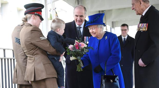 Two-year-old Alfie Lunn is held up by his mother Michelle as he hands a bouquet to the Queen while Prince Philip looks on during the unveiling of the new memorial at Victoria Embankment Gardens