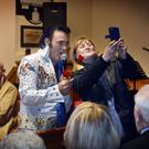 Elvis posing for a selfie with a member of the congregation