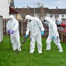 Police forensic officers conduct a search yesterday in Carrickfergus close to where George Gilmore was shot on Monday
