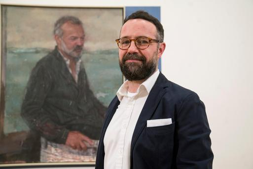 Belfast artist Gareth Reid with his winning portrait of TV presenter Graham Norton