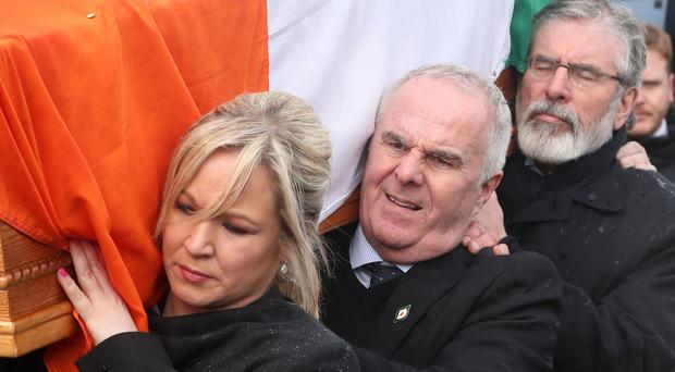 Michelle O'Neill helps carry the coffin of Mr McGuinness to his home in Londonderry