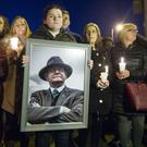 Roise Morgan holds an image of Martin McGuinness during a vigil at the former site of Andersontown police station in Belfast