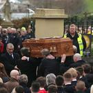 The coffin of Ryan McBride is carried into the Long Tower church in Londonderry