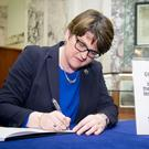 Arlene Foster signs a book of condolence at Belfast City Hall yesterday for the victims of the London terror attack
