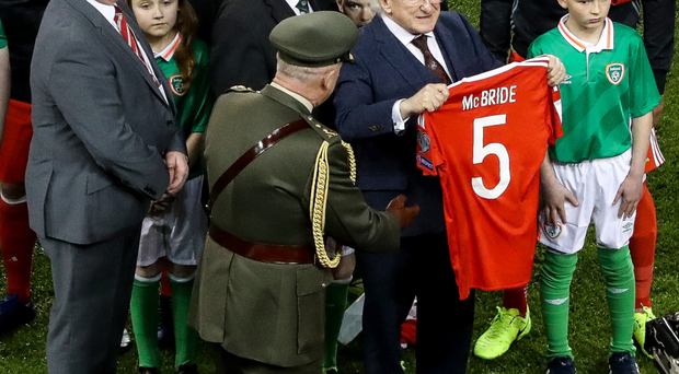 Irish President Michael D Higgins holds up the Derry City shirt of Ryan McBride at the Aviva Stadium