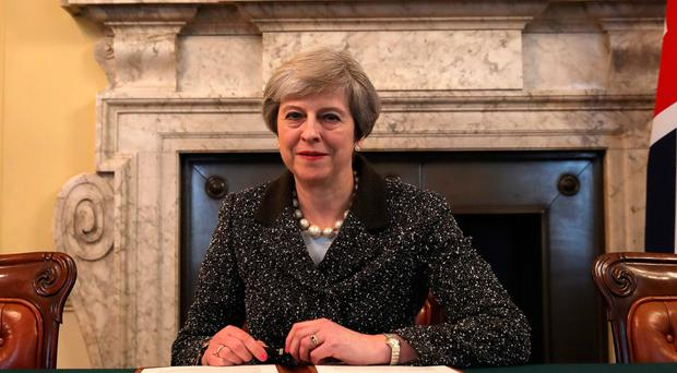 Prime Minister Theresa May smiles after signing the letter triggering Britain's proposed exit from the EU