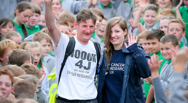 Dermot Breen and his daughter Hannah as he arrives back at Greenisland Primary School following his 1,000k walk for his wife Jacqui Breen