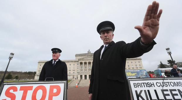 Anti-Brexit campaigners dressed as customs officers protest outside Stormont in Belfast