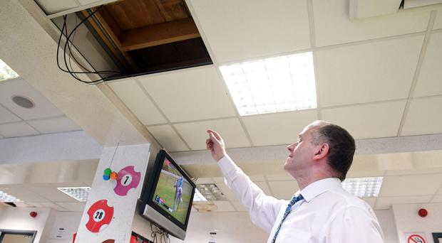 Kevin Devenney, of A.McLean's Bookmakers, examines damage caused during the attempted robbery