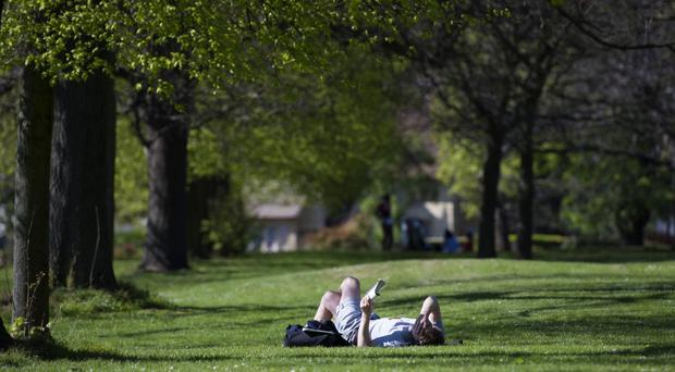 A man reads in Hyde Park, London, as temperatures soared