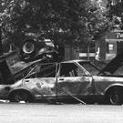 Forensic officers examine the remains of the IRA car which housed the Hyde Park bomb