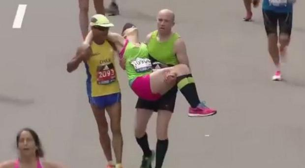 Terry (right) carries a struggling runner close to the finish line