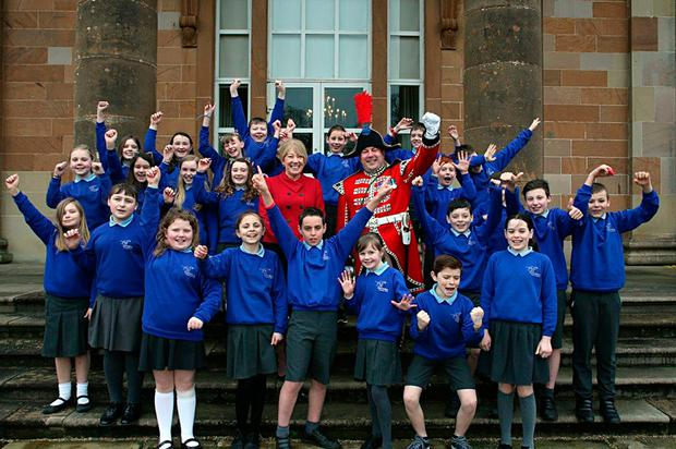 Pupils from Downshire Primary School with Patricia Corbett, head of Hillsborough Castle and Andrew Carlisle, bugler of the Hillsborough Guard, celebrate the news