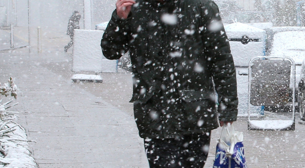 A person walks through a snow shower yesterday in Aviemore, Scotland